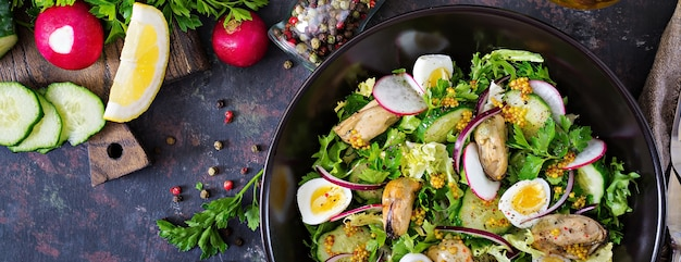 Диетический салат с мидиями, перепелиными яйцами, огурцами, редисом и салатом. здоровая пища. салат из морепродуктов. вид сверху. квартира лежала.