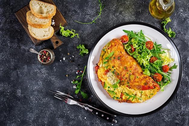 朝ごはん。トマト、アボカド、ブルーチーズ、グリーンピースと白い皿のオムレツ。フリッタータ-イタリアのオムレツ。上面図