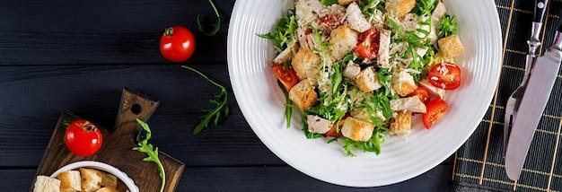 トマト、チーズ、クルトンのヘルシーチキングリルシーザーサラダ。北アメリカ料理。バナー。上面図
