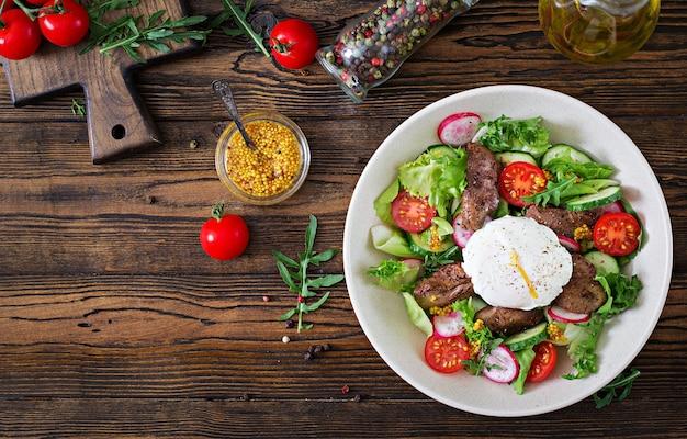 鶏レバー、大根、キュウリ、トマト、半熟卵の温かいサラダ。健康食品。トップビュー。平干し。