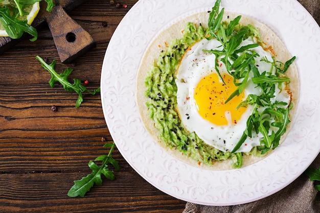 ワカモレ、目玉焼き、ルッコラのタコス。健康食品。便利な朝食。平干し。上面図