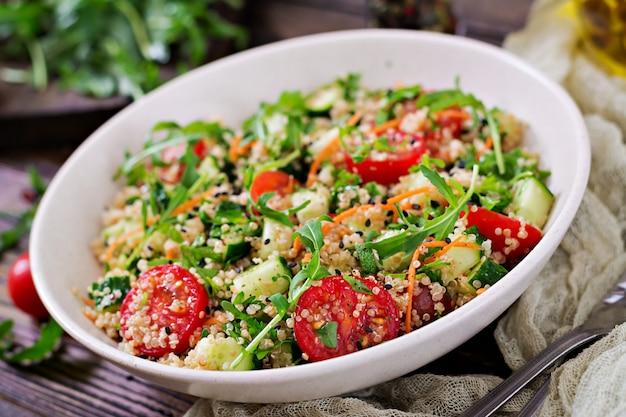 キノア、ルッコラ、大根、トマト、キュウリのボウルに木製のテーブルのサラダ。健康食品、ダイエット、デトックス、ベジタリアンのコンセプト。