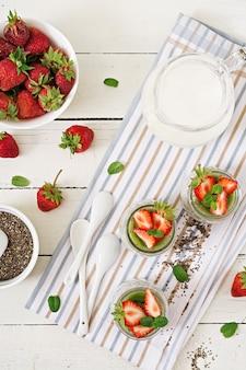 瓶の中のデトックスと健康的なスーパーフードの朝食。ビーガンココナッツミルクチアシードプリンとイチゴとキウイ。上面図。平干し。