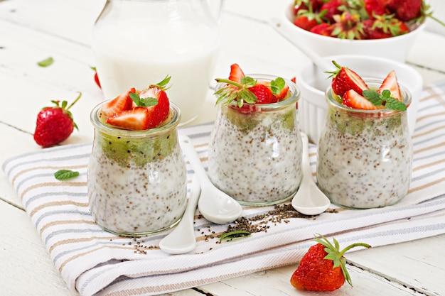 瓶の中のデトックスと健康的なスーパーフードの朝食。ビーガンココナッツミルクチアシードプリンとイチゴとキウイ。