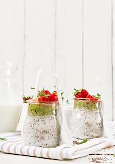 Детокс и здоровые суперпродукты завтрак в банке. веганские кокосовое молоко, семена чиа, пудинг с клубникой и киви.