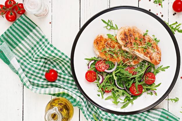 鶏ムネ肉のグリル、トマト、赤玉ねぎ、ルッコラの野菜サラダ。鶏肉のサラダ。健康食品。平干し。上面図。