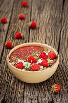 Детокс и здоровые суперпродуктов завтрак в миску. веганские чиа семена пудинг с клубникой и миндалем. клубничный смузи.