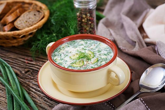 卵、キュウリ、木製のテーブルのディルと夏のヨーグルトの冷たいスープ。オクローシカ。ロシア料理