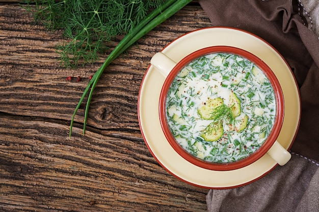 卵、キュウリ、木製のテーブルのディルと夏のヨーグルトの冷たいスープ。オクローシカ。ロシア料理。上面図。平干し。