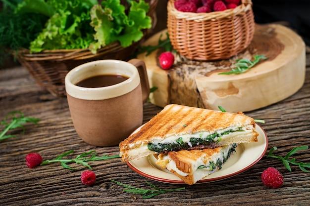 Панини бутерброд с сыром и листьями горчицы. утренний кофе. деревенский завтрак