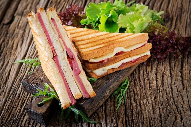 クラブサンドイッチ-木製テーブルの上のハムとチーズのパニーニ。ピクニックフード。