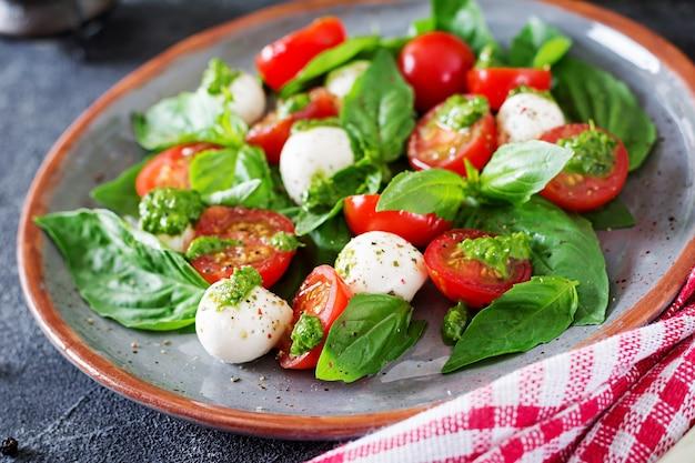 Салат капрезе. здоровая еда с помидорами черри, шариками моцарелла и базиликом. домашняя, вкусная еда. концепция вкусной и здоровой вегетарианской еды.