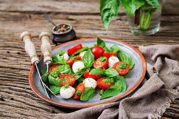 カプレーゼサラダ。チェリートマト、モッツァレラチーズのボール、バジルの健康的な食事。自家製のおいしい食べ物。おいしいと健康的なベジタリアン料理のコンセプト。