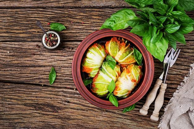 木製のテーブルの上のトマトソースに鶏ムネ肉を詰めたキャベツロール。おいしい食べ物。上面図。平置き