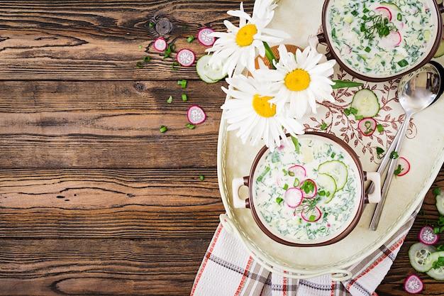 新鮮なキュウリ、木製のテーブルの上にボウルにヨーグルトと大根の冷たいスープ。伝統的なロシア料理-オクローシカ。ベジタリアンの食事。上面図。平置き