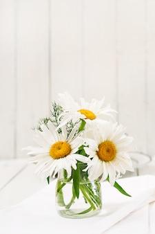 木製の白いテーブルの上に花瓶のヒナギクの花束