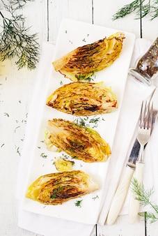 白い木製のテーブルにビーガングリルキャベツステーキ。健康食品。上面図。平置き