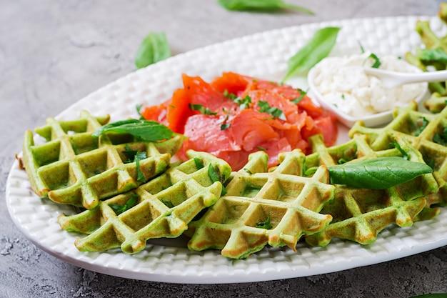 Пикантные вафли со шпинатом и сливочным сыром, лосось в белой тарелке. вкусная еда.