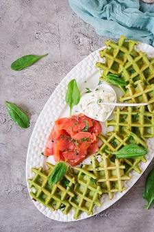Пикантные вафли со шпинатом и сливочным сыром, лосось в белой тарелке. вкусная еда. вид сверху. плоская планировка