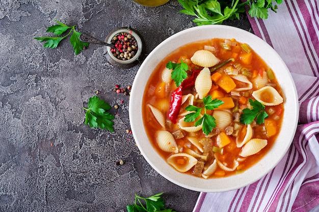 ミネストローネ、テーブルの上のパスタとイタリアの野菜スープ。ビーガンフード上面図