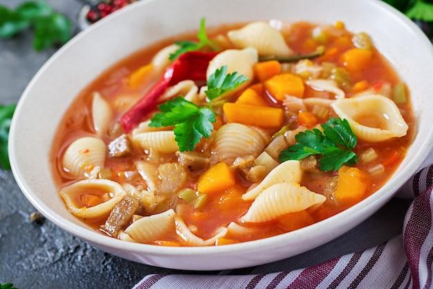 Минестроне, итальянский овощной суп с макаронами на столе. веганская еда