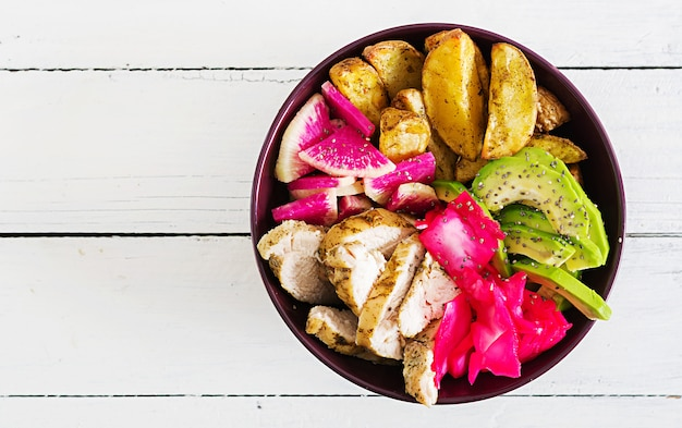 Блюдо из миски будды с куриным филе, картофелем, авокадо, капустой, редькой из арбуза и семенами чиа. детокс и здоровой пищи чаша концепции. вид сверху