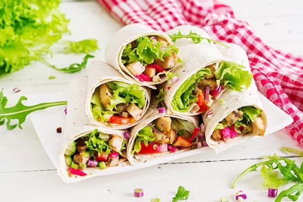 チキンブリトー。ヘルシーなランチ。メキシコのストリートフードのファヒータトルティーヤは、グリルしたチキンの切り身と新鮮な野菜で包みます。