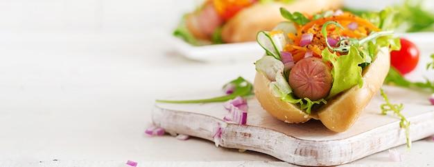 キュウリ、ニンジン、トマト、レタスと木製のテーブルのホットドッグ。