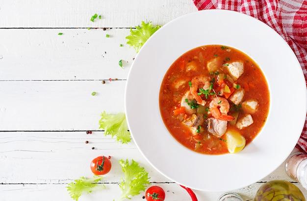 ブラジル料理:白い木製のテーブルの上の皿にスパイシーなココナッツソースの魚とピーマンのモケカカピクサバ。ブラジルの魚のシチュー。上面図