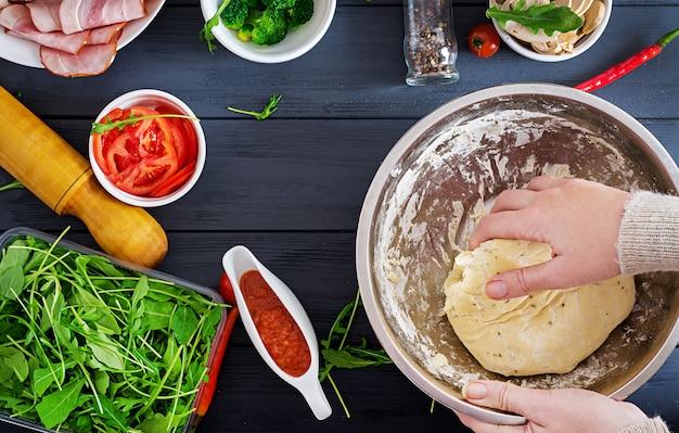 Итальянская пицца руки работают с тесто приготовления пиццы или пирога, делая ингредиенты на столе. тесто, сыр, помидоры, брокколи, грибы, салями, ветчина, куриное филе или выпечка. вид сверху