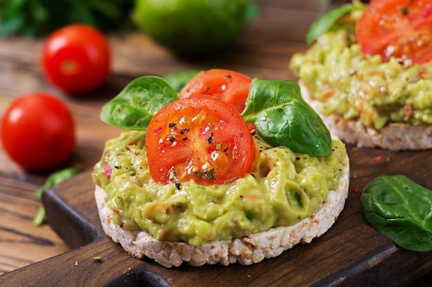 健康的な朝食。ワカモレと木製のテーブルにトマトのサンドイッチのぱりっとしたパン。