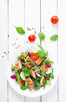 グリルした鶏の胸肉-トマト、きゅうり、大根、ミックスレタスの葉の新鮮野菜のサラダ。チキンサラダ。健康食品。