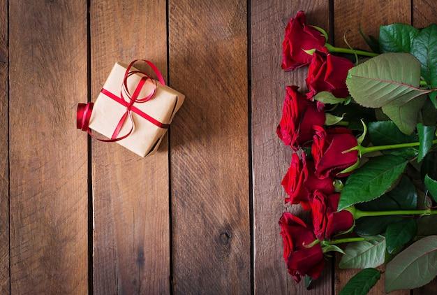 木製のテーブルに赤いバラの花束。