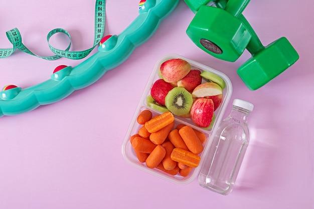 ジムの設備。健康食品。コンセプトの健康食品とスポーツライフスタイル。ベジタリアンランチ。ダンベル、水、ピンクのテーブルの上の果物。 。平置き