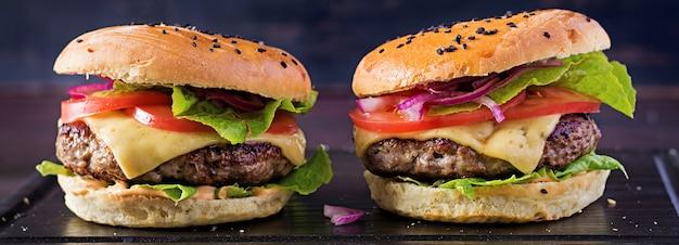 Большой бутерброд - гамбургер с говядиной, помидорами, сыром и листьями салата. баннер