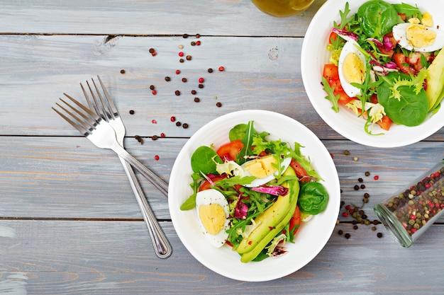 Вкусный и легкий салат из помидоров, яиц и микс листьев салата. здоровый завтрак. вид сверху