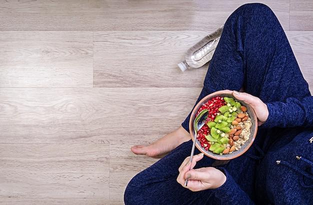 フィットネスと健康的なライフスタイルのコンセプト。女性は運動後休んで健康的なオートミールを食べています。上面図。
