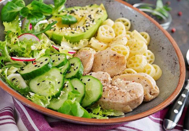 暗いテーブルでチキン、アボカド、キュウリ、レタス、大根、パスタのヘルシーサラダ。適切な栄養。食事メニュー。晩ごはん。