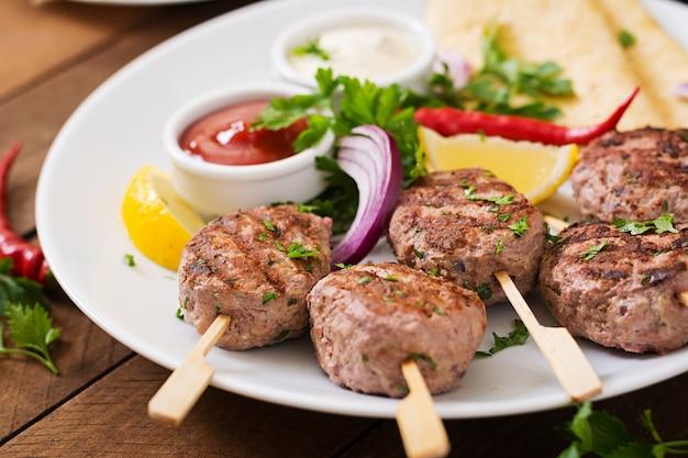 Аппетитный кофта кебаб (фрикадельки) с соусом и маисовыми лепешками на белой тарелке