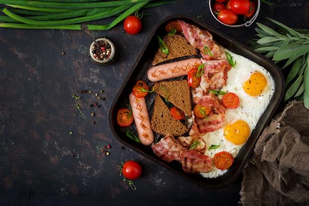 イングリッシュブレックファースト-目玉焼き、ソーセージ、トマト、ベーコン、トースト。 。平置き
