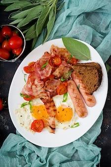 イングリッシュブレックファースト-目玉焼き、ソーセージ、トマト、ベーコン、トースト。