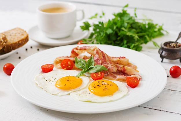 Английский завтрак - жареные яйца, помидоры и бекон.