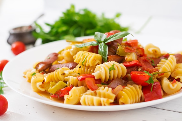 木製テーブルの上の白い皿に飾られたソーセージ、トマト、緑のバジルのトマトソースのパスタ。