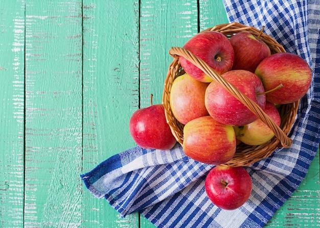 Спелые красные яблоки в корзине на ярком деревянном фоне.
