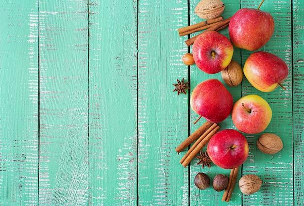 明るい木製の背景にバスケットで熟した赤いリンゴ。