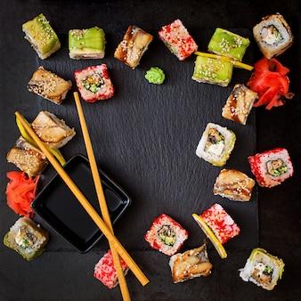 伝統的な日本食-寿司、ロール、黒の背景にソース。上面図
