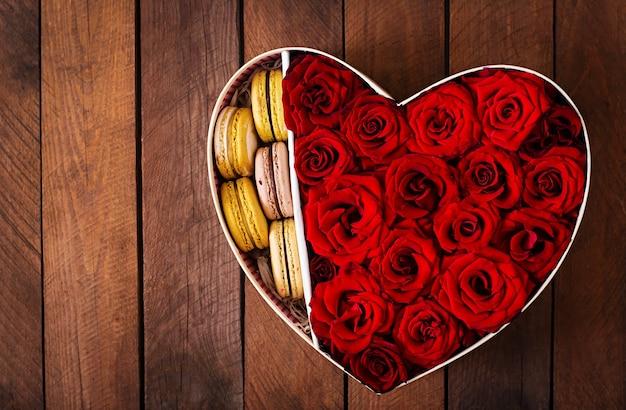 赤いバラとマカロンとハートの形をしたボックス。バレンタインデーのギフト。上面図