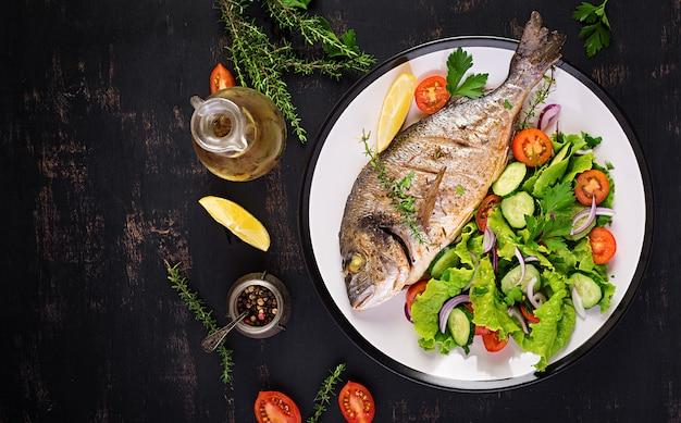 暗い素朴な背景に白い皿にレモンと新鮮なサラダと焼き魚ドラド。上面図。魚のコンセプトでヘルシーなディナー。ダイエットときれいな食事