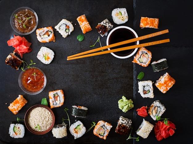 伝統的な日本食-暗い背景に寿司、ロール、ソース。上面図