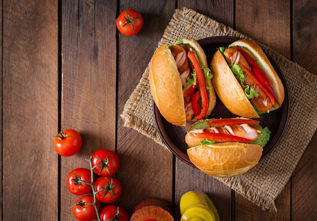 ホットドッグ-木製の背景にピクルス、パプリカ、レタスのサンドイッチ。上面図